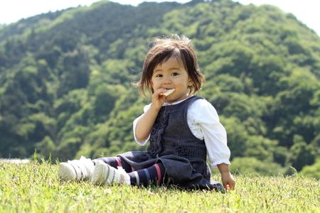 日本の女の子 (1 歳) おせんべいを食べる