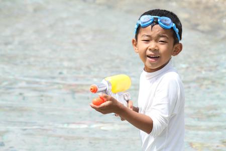 water gun: Japanese boy playing with water gun (first grade at elementary school) Stock Photo