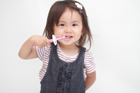 Japans meisje haar tanden poetsen (1 jaar oud)
