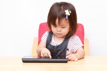 handheld device: Japanese girl using a tablet PC (1 year old) Stock Photo