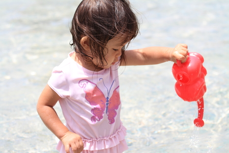 Japanese girl playing with water with watering pot (1 year old) Stock Photo