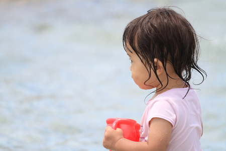 watering pot: Japanese girl playing with water with watering pot (1 year old) Stock Photo