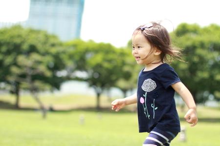 日本の女の子 (1 歳) の草の上を歩く
