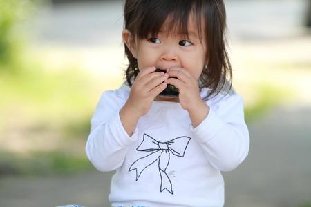 Japanese girl eating rice ball (1 year old)