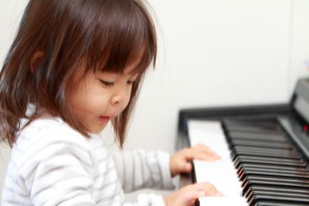 (2 歳) ピアノを弾く日本の女の子 写真素材