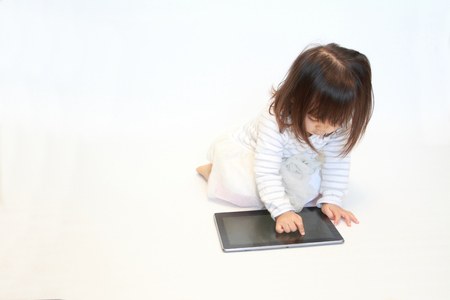 handheld device: Japanese girl using a tablet PC (2 years old)
