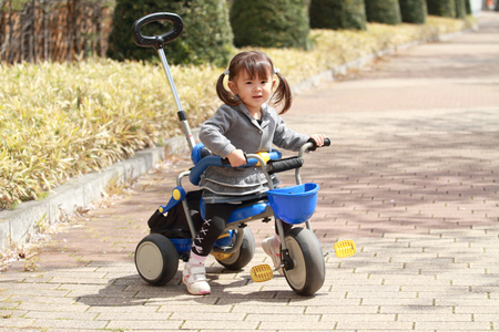 three wheeler: Japanese girl riding on the tricycle Stock Photo