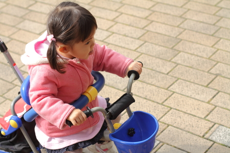 ciclos: Japanese girl riding on the tricycle (2 years old)