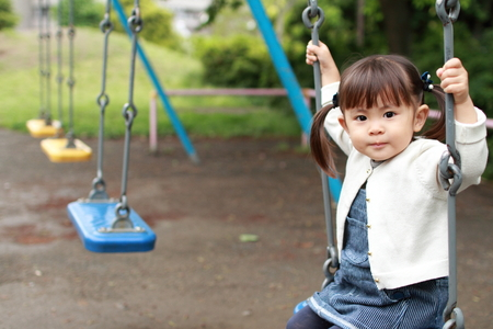 Japanese girl on the swing (2 years old) Stock Photo