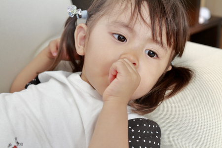 lying Japanese girl with sucking her finger (2 years old) Stock Photo