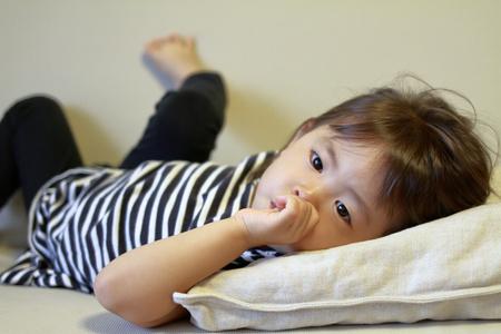 (2 歳) 彼女の指をしゃぶりで日本人の女の子を横になっています。