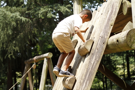 Japanese boy climbing on the wall (second grade at elementary school) Stock Photo