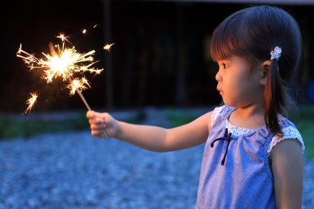 手持ち花火 (2 歳) を行う日本の女の子 写真素材
