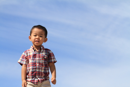 smiling Japanese boy under the blue sky (3 years old) in summer