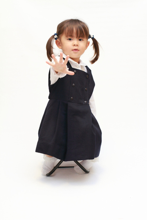 Japanese girl on the chair playing rock-paper-scissor in formal wear (2 years old) (paper) Stock Photo