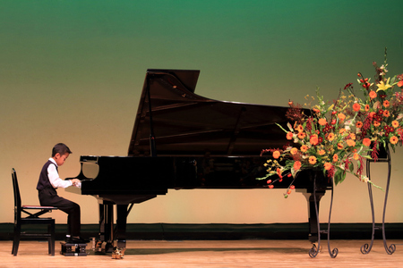 Niño japonés tocando el piano en el escenario (segundo grado en la escuela primaria)