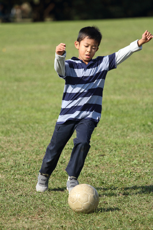 Japanese boy playing with soccer ball (second grade at elementary school) Stock Photo