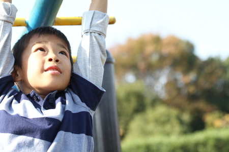 Japanese boy playing with a monkey bars (second grade at elementary school)