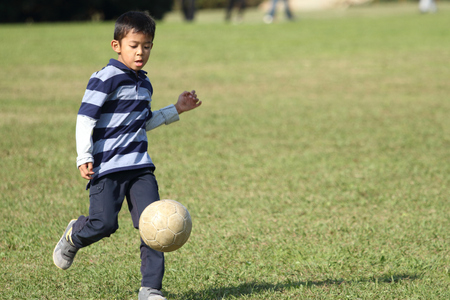 Japanese boy playing with soccer ball (second grade at elementary school) Imagens