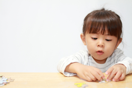 Japanese girl doing jigsaw puzzle (3 years old) 免版税图像 - 90462508