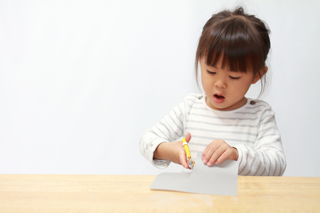 Japanese girl cutting paper with scissors (3 years old)