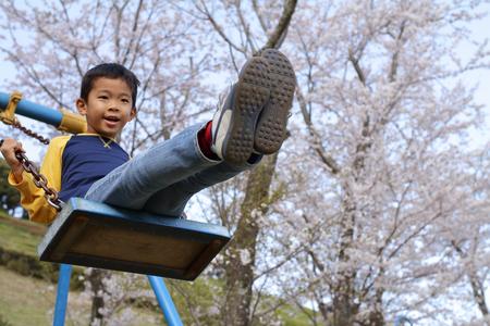 Japanese boy on the swing (third grade at elementary school) Archivio Fotografico