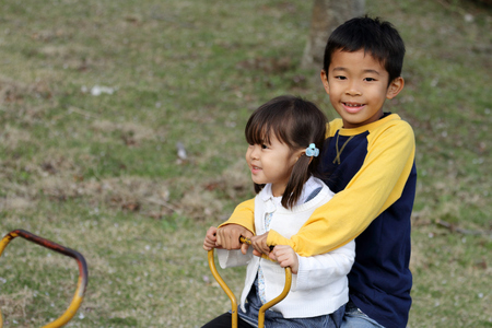 Japanese brother and sister on the seesaw (8 years old boy and 3 years old girl) Stok Fotoğraf