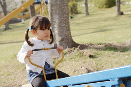 Japanese girl on the seesaw (3 years old) Stock Photo