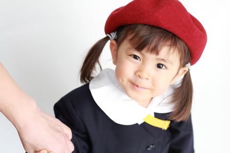 Japanese girl in kindergarten uniform clasping her mothers hand (3 years old) Stock Photo