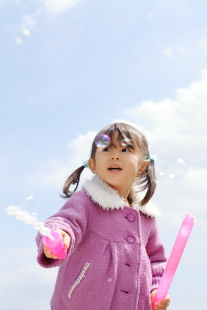 Japanese girl playing with bubble under the blue sky (3 years old) 写真素材