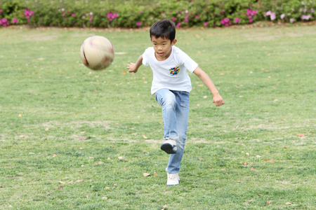 Japanese boy playing with soccer ball (third grade at elementary school)