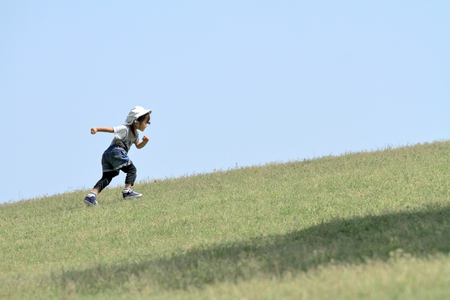 Japanese girl running up on the hill (3 years old)