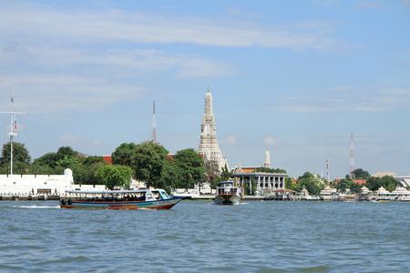 boat on Chao Phraya river and Wat Arun in Bangkok, Thailand