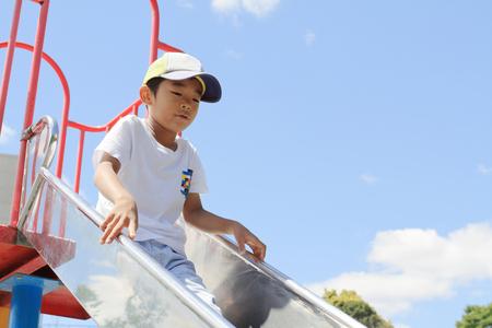 Japanese boy on the slide (third grade at elementary school) 写真素材