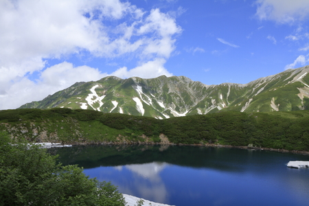 Mikurigaike pond and Tateyama mountain range with snow in summer in Toyama, Japan Standard-Bild - 107103845
