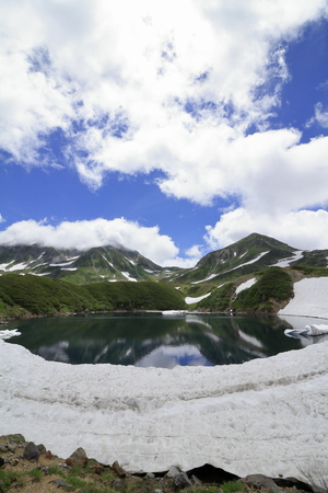 Mikurigaike pond and Tateyama mountain range with snow in summer in Toyama, Japan Standard-Bild - 107103848