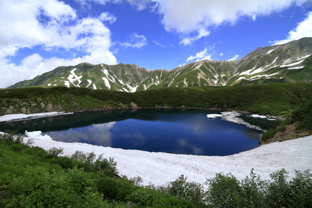 Mikurigaike pond and Tateyama mountain range with snow in summer in Toyama, Japan Standard-Bild - 110107098