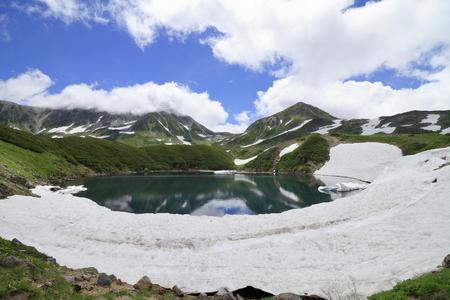 Mikurigaike pond and Tateyama mountain range with snow in summer in Toyama, Japan Standard-Bild - 110106834