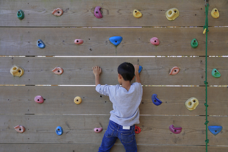 Japanese boy playing with bouldering (third grade at elementary school)