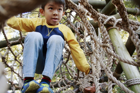 Japanese boy playing at outdoor obstacle course (third grade at elementary school)