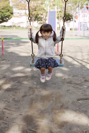 Japanese girl on the swing (4 years old) 写真素材