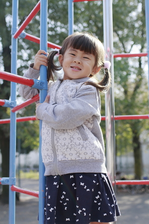 Japanese girl on the jungle gym (4 years old) 写真素材