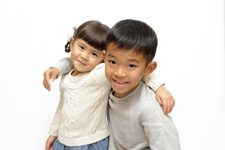 Japanese brother and sister putting arms around each other's sholders (9 years old boy and 4 years old girl) 免版税图像