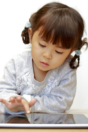 Japanese girl using a tablet PC (4 years old) Stock Photo