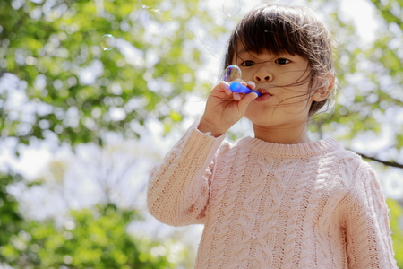 Japanese girl playing with bubble under the blue sky (4 years old) Stock Photo