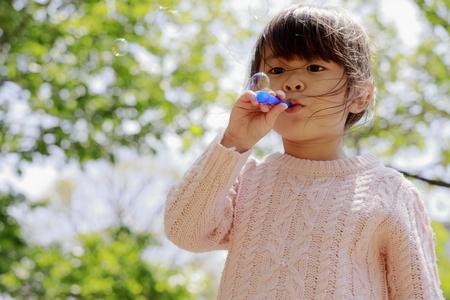 Niña japonesa jugando con burbujas bajo el cielo azul (4 años) Foto de archivo