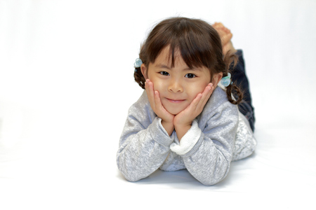 reclining Japanese girl with resting chin in hands (4 years old) Banco de Imagens