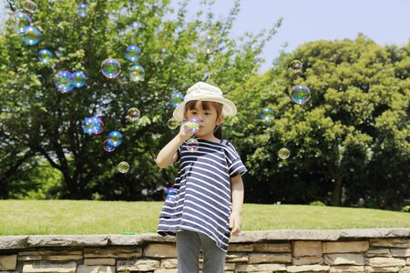 Japanese girl playing with bubble under the blue sky (4 years old) 免版税图像