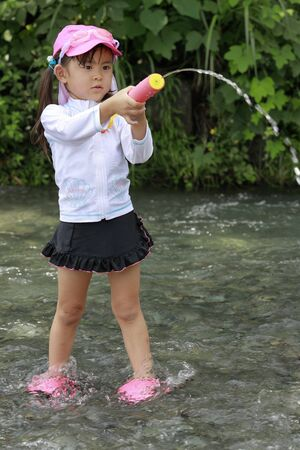 Japanese girl playing in the river with water gun (4 years old)