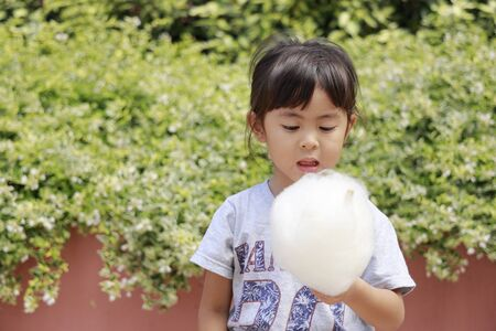 Japanese girl eating cotton candy (4 years old) Stock Photo
